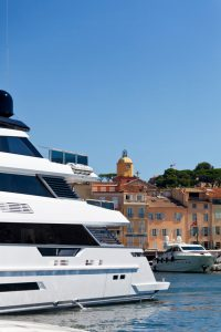 A luxury boat leaves St Tropez Harbour on the French Riviera. The iconic landmark of St Tropez, the church tower of Notre Dame of the Assumption church is in the background. Good copy space.